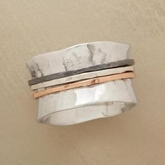 Three thread-slender rings in sterling silver, oxidized silver and 14kt rose gold twirl endlessly around the center of this concave hammered sterling silver band. Handcrafted. Whole sizes 5 to 9. This ring is licensed under U.S. patent nos. 6,497,117 and 6,395,732.
