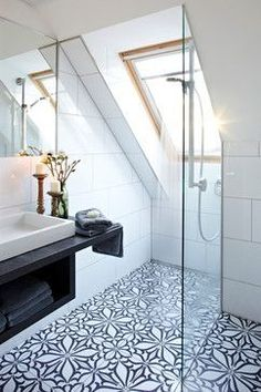 Funky monochrome patterned floor tiles really bring this modern attic bathroom alive!