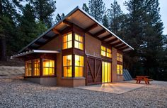 The shed roof rises to the south and allows winter sun deep into the living space. Large barn doors help temper solar gain and provide security when the homeowners are away. When open, the interior living space spills out onto the patio. The 872 sq.ft. cabin is a hybrid straw-bale home. @ http://www.finehomebuilding.com/item/23235/off-the-grid-straw-bale-getaway