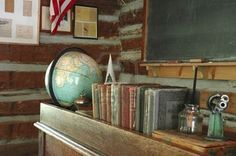 A teacher's desk and a chalkboard in an old-fashioned one-room schoolhouse.