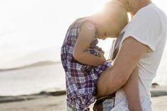 Mature man holding his toddler daughter on beach, Calvi, Corsica, France