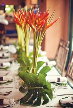 centerpieces made up of birds of paradise, orchids, and bamboo reeds, and other tropical flowers and foliage.