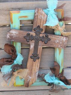 """A wooden turquoise painted frame with splashes of yellow, orange and brown holds a rustic wooden Cross in the center. The Cross is tilted to the side with a smaller black metal cross in the middle. Ties of turquoise and natural burlap and three different kinds of chocolate brown ribbon surround this beautiful Cross! Measures- 12 3/4"""" high X 9 1/2"""" wide"""