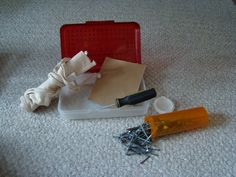 Tool kit contains nail apron, sandpaper, hammer or screwdriver, screws and nails.  Nails and screws are packed in a large medicine bottle. All contents fit neatly into a plastic school box!