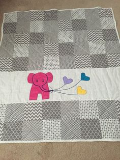 Measures approximately 40 by 45. Various gray and white squares surround a cute baby elephant hanging on to three heart-shaped balloons. Backed in a prewashed dark gray fleece and poly filled. Top-stitched. An adorable addition to any little ones room. Made in a smoke-free, pet-free home. Box 3