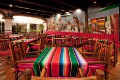 Líneas coloridas en manteles y sillas que hacen juego con el arte de la pintura.