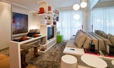 Uma estante vasada pra dividir os ambientes e a TV fica num suporte giratório. a mesa já no móvel é um plus