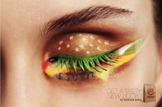 A closer look reveals that the contours of the model's eyes perform specific representations of the burger; for instance, the lid serves as the burger bun, the eyelashes are painted green for the lettuce, while the lower eyelids are colored with dashes of yellow, red, and brown to render the cheese, tomatoes, and burger patty, respectively.