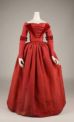 Unique red dress silk with red velvet ruching detailing at the elbows and as a faux collar on the bodice.  Horizontal tucks further enhance the bodice.  Gathered full skirt and tightly cinched waist.  Wide, shallow neckline, typical of this era (circa 1845-49) the Met Museum