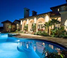 Maravilhosa a piscina junto com a iluminação da casa a noite