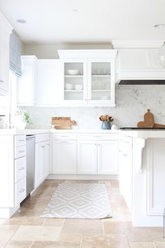 Fresh and bright, this coastal white kitchen is an inviting gathering spot for the whole family. Neutral, Tuscan-inspired tile grounds the space, while clean white cabinets open up and lighten the space. Calcutta marble subway tile is a glamorous backsplash, and the cabinets are topped with honed Calcutta marble featuring a clean, mitered edge.