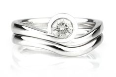 Asymmetrical engagement ring shown here with shaped wedding band.