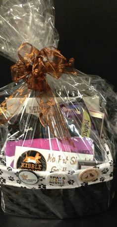 Item #5 Doggie Delight Basket. Includes: Kibble Kitchen magnet, ribbon magnet, tshirt, a neuter crew tote bag, note pad, button, book, cup with lid and straw all in a reusable basket. Perfect for dog lovers!
