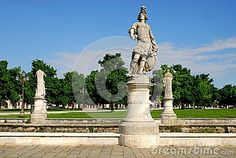 Photo made in Prato della Valle in Padua in Veneto (Italy). In the image, taken from the outside of the island Memmia exactly from the east, you can see in the foreground the statue pointing towards the target representing a young and proud man with long hair, behind and on either side are placed two statues look towards the green lawn, the trees and the deep blue sky.