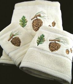 Made from 100% cotton, this 3 piece bath towel set is thick and thirsty. The embroidery is finely crafted and features a pine bough with pine cone, oak leaf and acorns on an ivory towel.