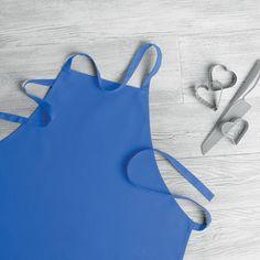 Delantal modelo Rever en color azul desplegado sobre una mesa