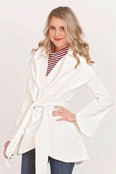 Winter white coat with wide lapel and tie at waist.
