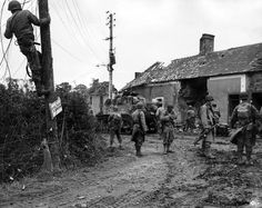 """Caption: """"U.S. Army soldiers of 2nd Battalion, 33rd Armor Regiment, move through the battle-scarred streets of Saint-Fromond as combat engineers repair communication lines during the Battle of Normandy. Saint-Fromond, Manche, Lower Normandy, France. 10 July 1944. Image taken by Rodger Hamilton."""""""