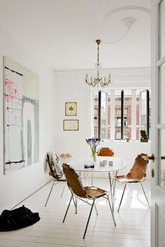 leather chairs, worn and stretched. paint everything white including the plank floors, add eclectic art and a simple chandelier