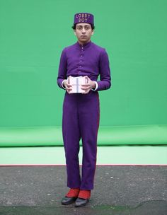 Tony Revolori as Zero, standing in front of a green screen, Mendl's box in hand | The Grand Budapest Hotel