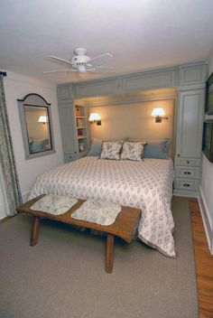"""""""built-in"""" bookcases turned inward toward the bed...maybe not cabinets over the top, though since there's a window. Maybe a shelf above the window with undercabinet lights instead of the integrated wall lamps?"""