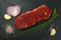 Raw beef steaks with ingredients on black slate board BBQ BBQ Time Beef Beefsteak Board Cuisine Food Food And Drink Freshness Healthy Eating High Angle View Ingredient Meat No People Onion Onions Preparing Food Raw Raw Food Red Slate Steaks Top Perspective Top View