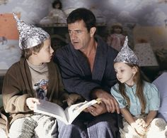 """Graham (Mel Gibson, center) tries to calm his children, Morgan (Rory Culkin, left) and Bo (Abigail Breslin, right), who think that tin foil hats can stop aliens from reading their minds, in """"Signs"""""""