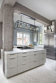 Herringbone brick floor + soft palette + historical beamwork + modern lighting in kitchen by Ty Larkins