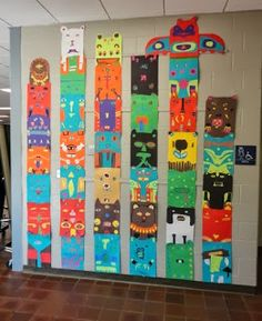 Thomas Elementary Art show video of totem poles and stylized animals, draw animal different from anyone at their table, cut out construction paper to make animal using colors of Northwest Indians, put table number on back, hang each table as a totem pole.
