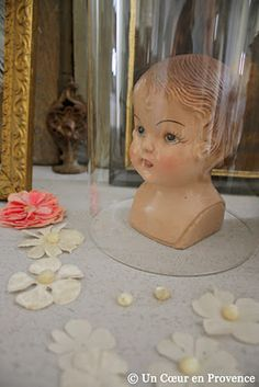 Old doll head under glass dome.  It whispers terrible things to you at night.