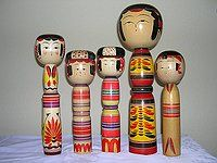 Yajiro Dolls    Yajiro dolls are easily recognizable by their signature waistline and colors. This doll has a dominant yellow base for its body with purple, black, blue and red designs. The various patterns range from stripes to flowers. Some of these dolls also have a topknot hairdo.