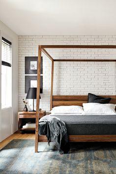 White brick wall behind bed