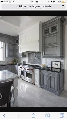 White And Gray Kitchen Features Gray Wash Cabinets Paired With Black Granite  Countertops And A Gray And White Marble Slab Backsplash.