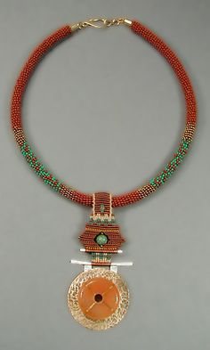 """Santa F'Asian Necklace""    Collar is wrapped seed beads and is 18"" long. An ornament of hammered brass and silver with a carnelian stone is hung from knotted nylon cord with a turquoise bead at center. Pendant is 3.5"" long.    Price 450.00    Item #J-P8310015    Contact me about availability."