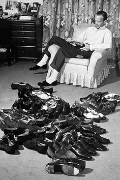 Fred Astaire filing smooth the metal of tap on a dance shoe as he sits next to a pile of 34 of his 84 paris of dancing shoes at home, photographed by Bob Landry, 1941.