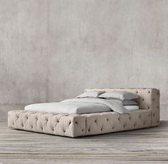 RH's Soho Tufted Fabric Platform Bed:With its plushly padded headboard and wide wraparound rail, our grandly proportioned Soho bed is comfort writ large. Its allover button tufting recalls classic Chesterfield furniture