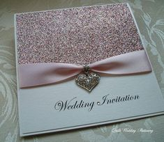 Got bling? Pink glitter wedding invitation wrapped with pink satin ribbon threaded through a diamante heart. Swarovski crystals adorn the wording on the front from Quills Wedding Favours via Etsy