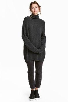 Een lange, zachte gebreide coltrui met raglanmouwen. De trui heeft een ribgebreide boord aan de onderkant en onder aan de mouwen.