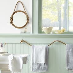 Channel your inner deckhand and get the bathroom shipshape with easy rope-based decorations (anyone who can tie a knot can make these). To set up the towel holder, use a 1/2-inch natural-fiber rope from a home-supply store. Secure a series of large screw eyes to the wall; feed the rope through, and knot. Round table mirror, jamaligarden.com. Guest towels, in Grey/White, Shirt stripe towels, and Bleach Maple Natural-Edge bowl, 7 inches by 5 inches abchome.com. Rope Mirror How-To…