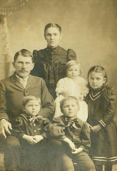 """Captioned: """"Peter B. Krehbiel / Katie S. Krehbiel / Jacob / Walter / Elmer / Emma."""" Written with shakey handwriting - Emma? Pictured clockwise from left, according to the caption: Peter Krehbiel, Katie, Walter (baby in white), Emma, Elmer, Jake. Moundridge, Kansas. Date unknown but probably within a year of Jake's birth in December 1898. Digitally retouched by Tom Krehbiel to remove defects."""