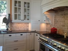travertine backsplash design with white cabinets and black countertop