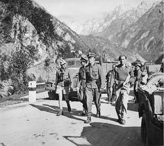 """Two officers of 1.SS Panzer Division """"Leibstandarte SS Adolf Hitler"""" proceed to the location of the British 6th Armoured Division to surrender their unit on a mountain road in Austria, May 7, 1945."""