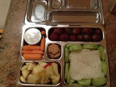 "A planet box lunch with dinosaur sandwiches (  herb and garlic cream  cheese and cucumbers) with cucumber "" fences"", baby carrots with dip, mini chocolate chip cookies, chopped apples, and grapes"