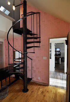 スウィートなピンクの壁紙に、アイアンの螺旋階段がよく似合う。上のロフトが子どもたちの寝室。