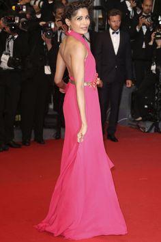 Festival de Cine de Cannes 2013. Freida Pinto apostó por el rosa fucsia con un vestido de chifón de Gucci con escote cruzado y cinturón dorado al que añadió unos pendientes de Chopard.