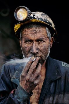 "Coal Miner, Pul i Khumri, Afghanistan, 2002 ""A coal miner, dark with the dust from the mine, slowly registers his presence against the darker field of the mine's deep shaft in central Afghanistan. Light from his lamp and the trail of white smoke from his cigarette focus attention. Then the whites of his eyes emerge, then his fingertips. Gradually he appears. This difficult image mirrors the tough lives of miners in Afghanistan, men who live perilously under threatening conditions.""…"