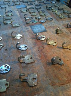 chave contorcida que serve como gancho para pendurar colares, brincos, pulseiras