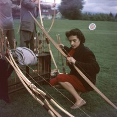 A female archer kneels down with a bow while practicing archery in Stanley Park, Vancouver, B.C., 1954.