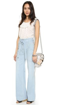 These wide-leg Ulla Johnson jeans are fashioned with a charming, optional tie at the waist. Rounded seams define the hip pockets. Hook-and-eye closure and zip fly.