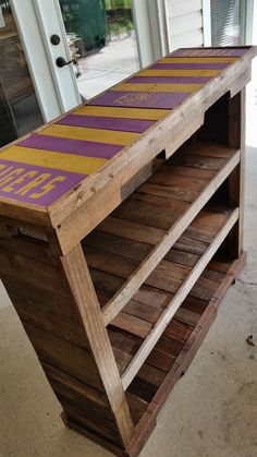 "RECYCLED WOOD PALLETS: We got a request to make and LSU bookcase. Here it is!. If you like the top but would rather this be a coffee table, Bistro table or console table, message us and let us know what you want. This large sturdy bookcase has an LSU Tigers team logo painted on the top. It is 44"" L x 14"" W x 42"" H, it sells for $85 as is and $100 if we stain it for you. Keep watching, because I have been asked to do a MSU bookcase that is going to be used as a mini bar. Item # 323"